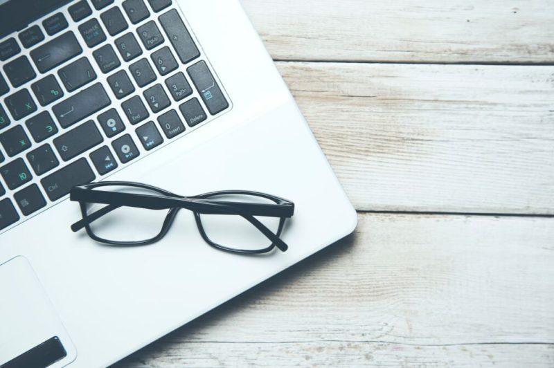 ノートパソコンとメガネの画像